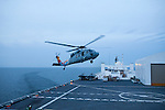 A helicopter arrives on the flight deck of the USNS Comfort, a naval hospital ship, as it makes its way to Haiti to help earthquake survivors on Saturday, January 16, 2010 in the Chesapeake Bay.