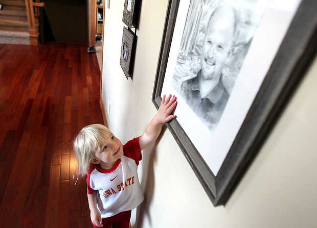 "Ella Jacobs, 3, reaches up to touch a drawing of her father, Eric, who died in a plane crash before she was born in 2006.  The drawing, created by Eric's brother, xxxxx, is the centerpiece of the Jacobs' living room in their Polk City home, where Ella's mother, Heather and her four brothers honor his memory.  Even though Ella never met Eric, she delightfully refers to him as her ""angel in heaven."""