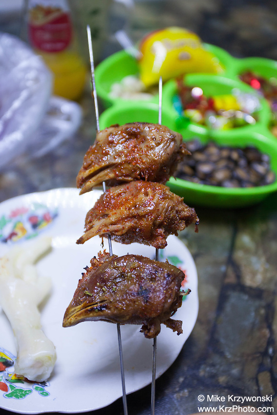 Cooked chicken heads on a skewer ready to be eaten in China