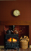 A fire blazes in the wood burning stove in front of a wall covered in red tartan