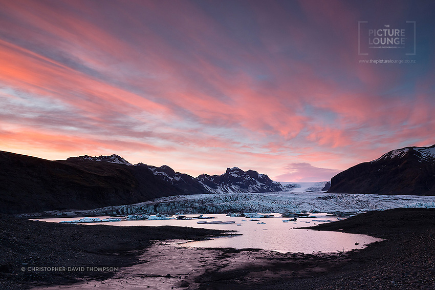 A stunning midnight sunset over the glacial lagoon in the Vatnjökull National Park at the base of the Skaftafellsjökull glacier, in Southern Iceland.