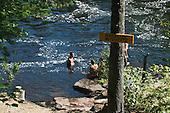 """Personnes adulte  qui se baigne dans la riviere l'Assomption au parc  régional des chutes Monte-à-Peine a Saint-Jean-de-Matha,  sous une pancarte jaune indiquant """" Baignade Interdit"""""""