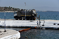 Pictured: Specialist crew work to contain the oil spill that has reached the coast of Salamina, Greece<br />
