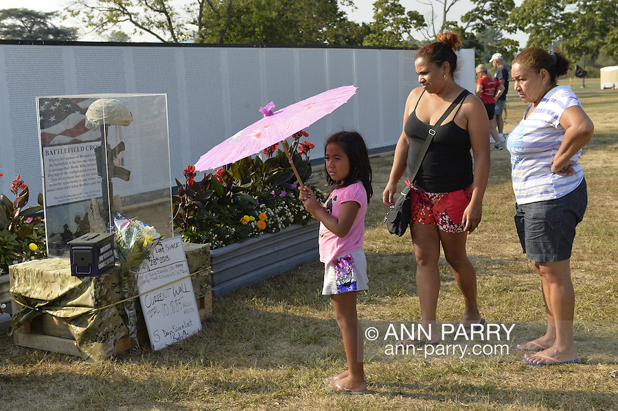 "East Meadow, New York, U.S. 11th September 2013. A young girl and family look at the Battlefield Cross display at the Global War on Terror ""Wall of Remembrance"" a traveling memorial on display in New York for the first time, at Eisenhower Park on the 12th Anniversary of the terrorist attacks of 9/11. The unique 94 feet long by 6 feet high wall has, on one side, almost 11,000 names of those lost on September 11, 2001, along with heroes and veterans who lost their lives defending freedom of Americans over past 30 years. On the wall's other side is a timeline, with photos, covering 1983 to present day."