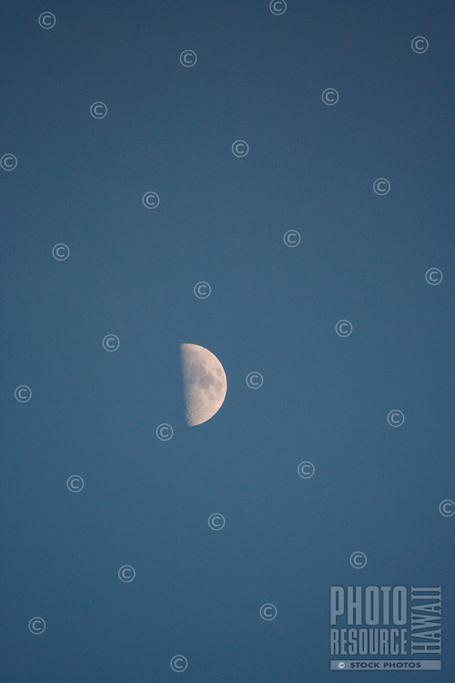 Half the moon is visible in a blue sky, Hawai'i.