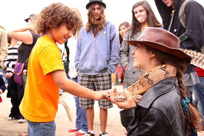 William Begley, 6, leans in to touch a Boa Constrictor hanging around Jenna Watkins neck at the Boomslang carnival outside Buster's Billiards and Backroom on Saturday, Oct. 10, 2009. Photo by Scott Hannigan | Staff