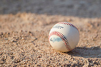 A South Atlantic League baseball sits on the dirt behind home plate at Fieldcrest Cannon Stadium on May 22, 2011 in Kannapolis, North Carolina.   Photo by Brian Westerholt / Four Seam Images