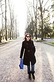 ITALY, Venice. Artist Mia Kaplan walking along the tree lined Viale Giuseppe Garibaldi in the Castello district of Venice. Castello is the largest of the six sestieri of Venice.