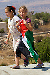 Two Palestinian girls walk across a rooftop the West Bank village of An Nabi Salih near Ramallah on 09/07/2010.
