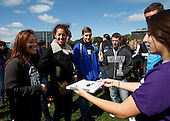 Northwestern freshmen are offered a chance to win a signed jersey from Coach Fitzgerald by writing their hometowns on a dry erase board and posing for photos.
