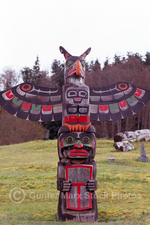 Kwakwaka'wakw (Kwakiutl) Memorial Totem Pole on Namgis Burial Grounds, Alert Bay, Cormorant Island, BC, British Columbia, Canada - Thunderbird sits above Man holding Copper