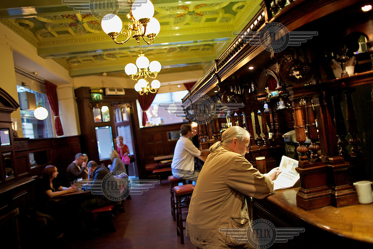 A man reads a newspaper at the bar of the Abbotsford pub on Rose Street in Edinburgh.