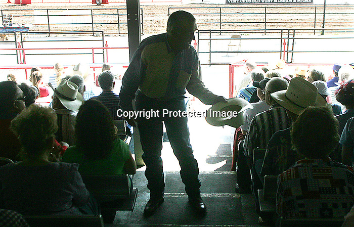MICHAEL SMITH/WTE..Minister/cowboy poet Gabe Pennel of Purdy, MO passes the collection cowboy hat during Cowboy Church services in the stands of the rodeo arena at Frontier Park.