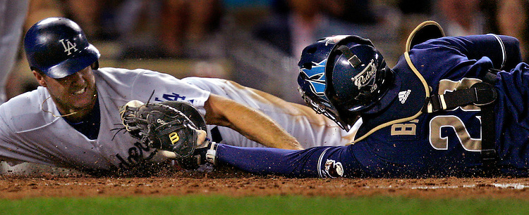 Dodger Jeff Kent, left, grimaces as he gets tagged out at the plate by San Diego Padre catcher Michael Barrett while trying to score from third base on a fly ball by Russell Martin during third inning at Dodger Stadium in Los Angeles Thursday September 13, 2007.