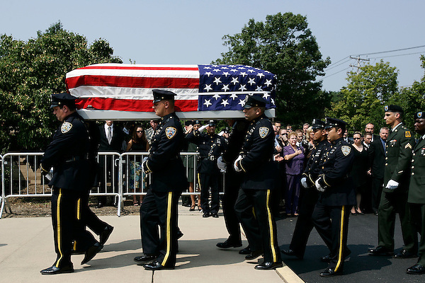 Thousands of police officers and military turned out for the funeral of James McNaughton, the first NYPD officer killed in the war in Iraq. James McNaughton's casket is carried into St. Elizabeth Ann Seton Church. His family stands behind. (From right to left front row)<br />Father, William: stepmother, Michelle: fiancee Liliana Paredes. All others were unidentified.