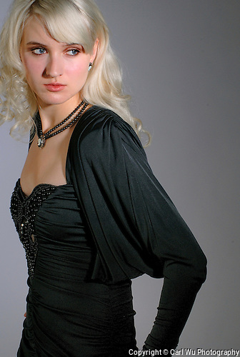 Model Wearing Long Black Dress With Gray Background.