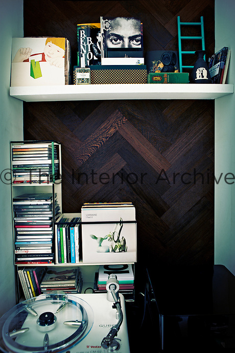 An individual display of personal items in a shelved recess with a wooden herringbone pattern behind. Compact discs, a record deck and other items are neatly arranged.