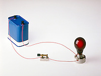 SIMPLE CIRCUIT<br /> (2 of 2)<br /> 12V battery, closed switch, lit bulb<br /> The negative terminal of the battery pushes electrons towards the positive terminal which attracts the electrons. This current travels across the bulb filament where resistance causes the filament to heat up and glow.