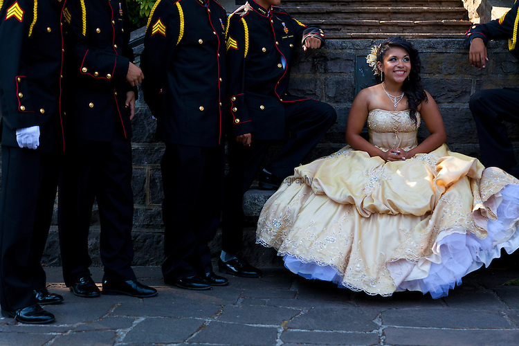A young woman flanked by men in uniform at the rose garden in Portland, Oregon in celebration of her quinceanera.