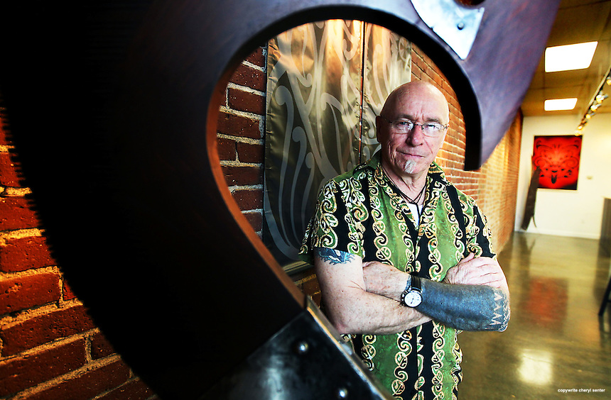 Artist ,Trevor Marshall, is surrounded by his passion for art, including a recently completed wood and metal sculpture, in forground, and paintings, in background, in his Islington St. studio, Oceanic Tatau, in Portsmouth, N.H., Sunday, March 25, 2012. (Portsmouth Herald Photo Cheryl Senter)
