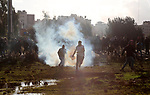 Palestinians run for cover from tear gas during clashes with Israeli soldiers near the Jewish settlement of Beit El, in the West Bank city of Ramallah, on December 13, 2018. A Palestinian shot dead two Israeli soldiers at a bus stop in the occupied West Bank, the military said, sparking raids in the West Bank city of Ramallah in which one Palestinian was killed. The attack came hours after security forces killed two Palestinian murder suspects, with fears of wider unrest. Photo by Ahmad Arouri