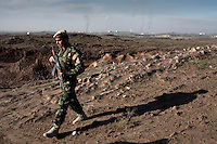 A Peshmerga soldier walks across mined wasteland on the outskirts of Kirkuk. The Baba Gurgur oil refinery is visible in the background.