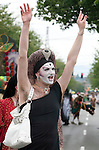 A participant with an elaborate face paint waves to friends in the crowd in the 21st annual Summer Solstice Parade held Saturday, June 20, 2009 in Seattle, Wa. The parade was held Saturday, bringing out painted and naked bicyclists, bands, belly dancers and floats. (Jim Bryant Photo © 2009).