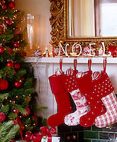 Red and white patchwork Christmas stockings hang from the mantelpiece next to the Christmas tree