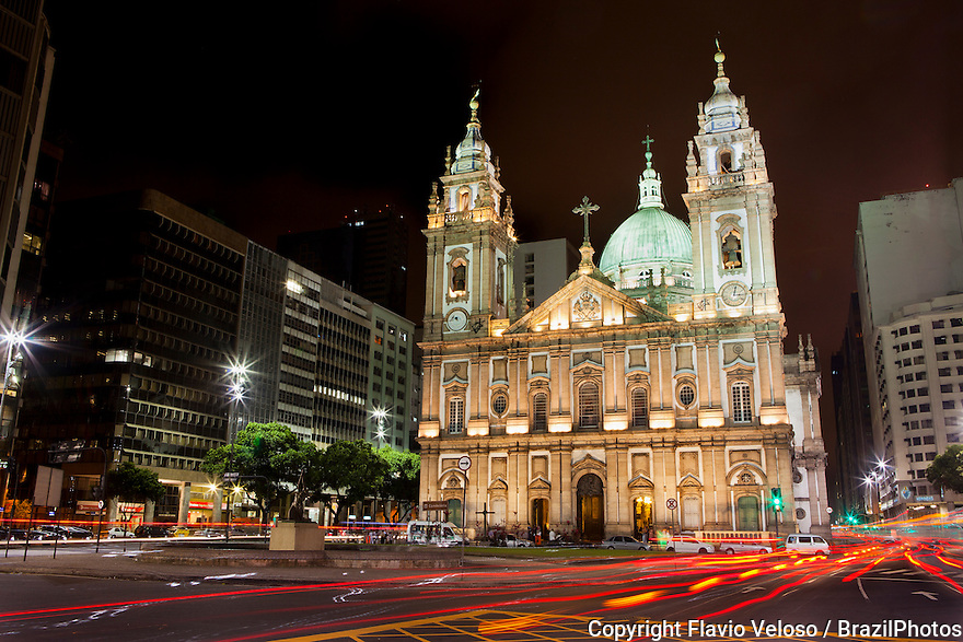 The Candelaria Church ( Portuguese: Igreja Nossa Senhora da Candelaria ) is an important historical church in dowtown Rio de Janeiro, Brazil, that combines a Baroque facade with a Neoclassical and Neo-Renaissance inner decoration - it is a Latin cross church with a dome over the transept. The main facade shows Baroque influences in the design of the windows, doors, and towers, as well as Neoclassical influences in the bi-dimensionallity of the facade and the triangular pediment. The facade contrasts the dark granite of windows, columns and other elements with whitewashed wall segments, a typical characteristic of colonial churches in Rio. The nave has three aisles and a main chapel in the apse. The whole ensemble seems inspired by the church of the Convent of Mafra and in the Estrela Basilica of Lisbon, both in Portugal.
