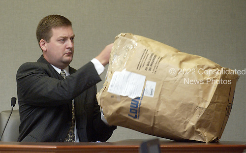 Montgomery County (Maryland) Police forensics specialist David McGill opens a bag containing a duffle bag found in the Chevrolet Caprice when sniper suspect John Allen Muhammad was arrested during his testimony in courtroom 10 at the Virginia Beach Circuit Court in Virginia Beach, Virginia on November 3, 2003.<br /> Credit: Lawrence Jackson - Pool via CNP