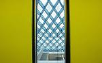 Yellow Elevator doors open onto the diamond cross hatch of the library's floor.