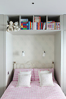 A child's bedroom with built-in storage and decorated with friendly polar bear wallpaper