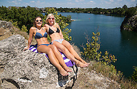Two sexy young women suntanning at the tranquil Quarry Lake, Austin, Texas.