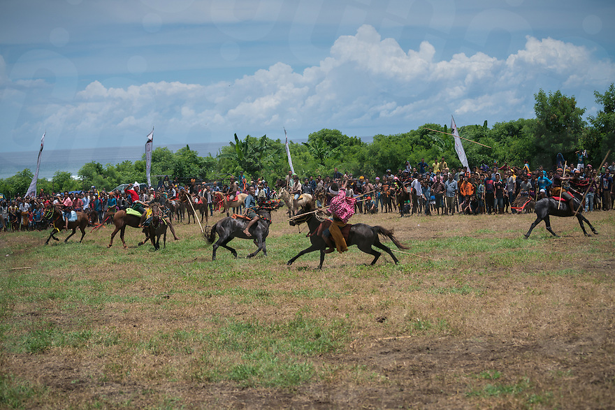 March 26, 2016 - Ratenggaro (Indonesia). Pasola riders throw their spears hoping to strike a member of the opposing clan. Riders are grouped into 2 teams, based on their traditional clans. The aim of the Pasola is to throw blunted wooden spears at the opposition riders while trying to avoid their counter attacks. © Thomas Cristofoletti / Ruom