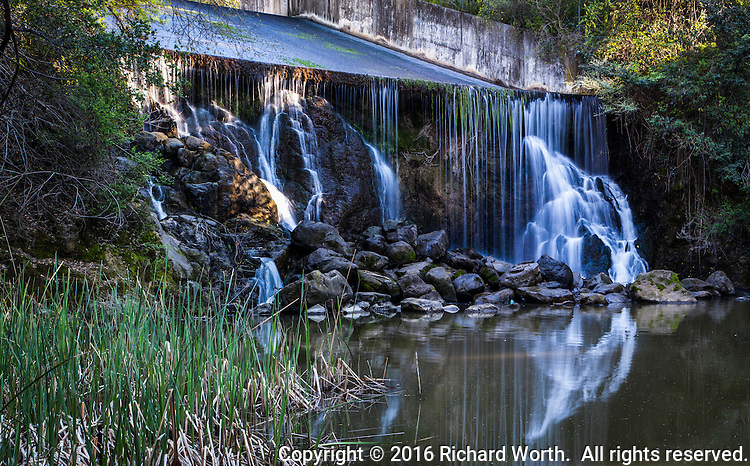 Three images combined to provide a wide, panoramic view of the man made waterfall - excess water from the San Lorenzo Creek reservoir flowing over the spillway.