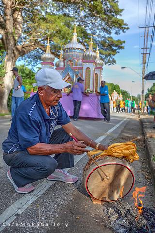 Drummer heats the skin of a tassa drum, Hosay, Muslim festival parade, Port of Spain, Trinidad