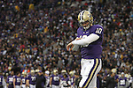 Jake Locker (#10), University of Washington quarterback, stands alone amid a sea of people checking his play sheet during the Huskies Pac-10 conference football game against arch-rival Washington State at Husky Stadium in Seattle, Washington, on November 28, 2009.  Washington shut out the Cougars in their annual Apple Cup battle, 30-0.