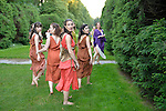 Old Westbury, New York, U.S. - June 21, 2014 - Lori Belilove & The Isadora Duncan Dance Company, while walking down the South Alee, turn around to look back at the South Lawn where they will soon perform their finale of Midsummer Night event at the Long Island Gold Coast estate of Old Westbury Gardens on the first day of summer, the summer solstice. Ms. Belilove is wearing a white tunic and purple over-scarf.