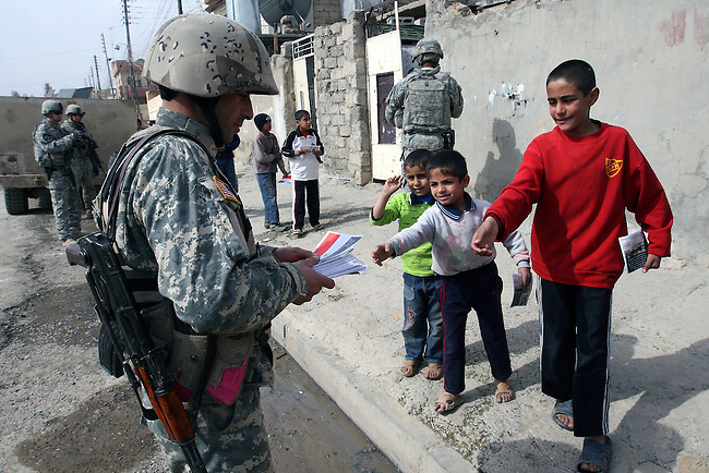 An Iraqi soldier hands out leaflets to local boys during a patrol with U.S. forces in Mosul, Iraq. The leaflets urge civilians not to cooperate with terrorists and to call in tips on al Qaida and other insurgents. U.S. commanders say a new string of combat outposts and daily patrols by U.S. and Iraqi troops are pushing insurgents out of the city. March 1, 2008. DREW BROWN/STARS AND STRIPES