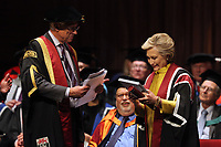 Pictured: Hillary Clinton on stage is being handed a commemorative book of her family tree at Swansea University Bay Campus. Saturday 14 October 2017<br />
