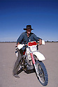 "A jackaroo, with motorbike, mustering on ""Bulloo Downs"" station, near Thargomindah, outback Queensland."