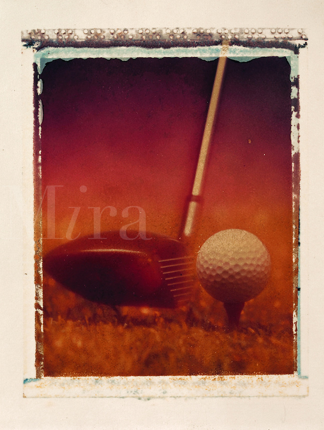 Detail of a golf ball and driver.