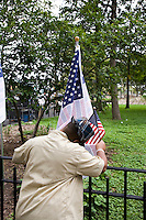 A man looks at one of three thousand flags displaying the names of the victims of the September 11th attacks in Battery Park in New York City, New York on the 10th anniversary of the September 11th attacks on 11 September 2011 in an effort to provide all New Yorkers who lived through the events of 9/11 a public place to gather and pay respects to those who were killed that day.
