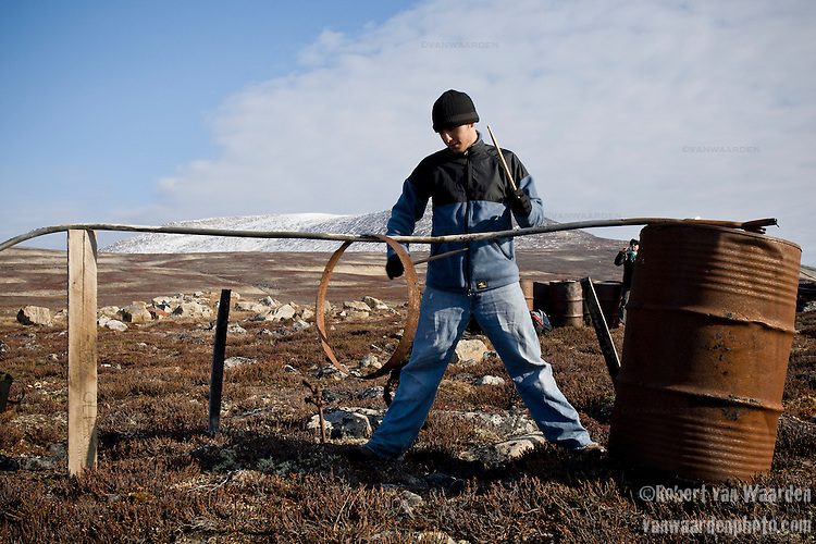 A young man makes music with drumsticks on old military garbage in Northern Canada, Nunavut. The man is part of the Cape Farewell Youth Expedition that was organized by the British Council of Canada. He is playing in an impromtu concert designed as part of a program to use art to communicate climate change.