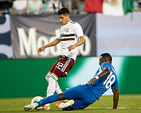 CHARLOTTE, NC - JUNE 23: Samuel Camille #18 tackles Uriel Antuna #22 during a game between Mexico and Martinique at Bank of America Stadium on June 23, 2019 in Charlotte, North Carolina.