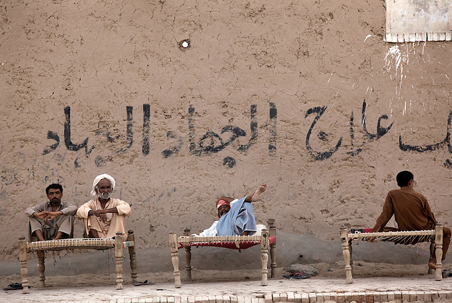 25 JULY 2011: Basti Mahraan Village, Punjab, Pakistan.  Muslim village men recline on rope beds during a searing day.  Mahar Abdul Latif, a former member of Muslim terrorist group Lashkar-i-Taiba (LeT) found his views towards Hindu's change after  Bachu Ram, a Hindu offered to donate his rare blood type to save the life of a Muslim woman. As a result relations  have thawed in the traditional violence between the Muslims and Hindu's of the village. Picture by Graham Crouch/Toronto Star.