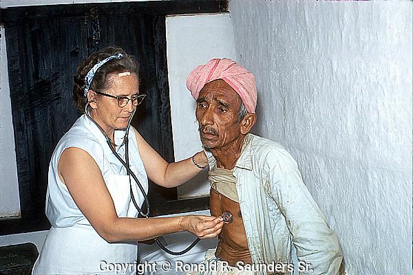 VOLUNTEER NURSE CHECKS the PULSE of a POOR INDIAN MAN