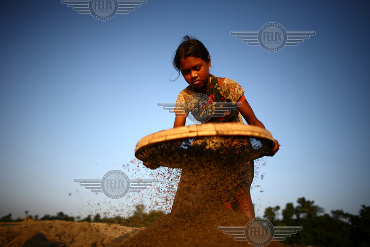 A child sifts sand at Bhollar Ghat. At least 10,000 people, including 2,500 women and over 1,000 children, are engaged in stone and sand collection from the Bhollar Ghat on the banks of the Piyain river. Building materials such as stone and sand, and the cement which is made from it, are in short supply in Bangladesh, and commands a high price from building contractors. The average income is around 150 taka (less than 2 USD) a day..