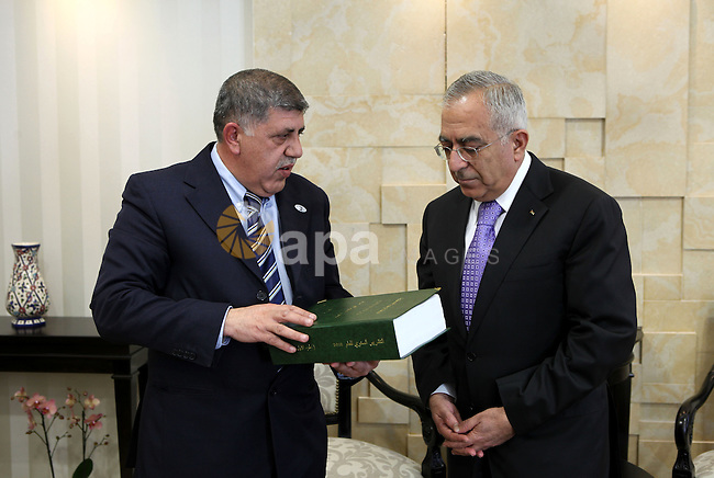 Palestinian Prime Minister, Salam Fayyad receives the report of the office of management and financial controls for 2010, in the West Bank city of Ramallah on March 2, 2011. Photo by Mustafa Abu Dayeh