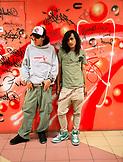 MALAYSIA, Kuala Lumpur, portrait of teenagers standing against graffiti